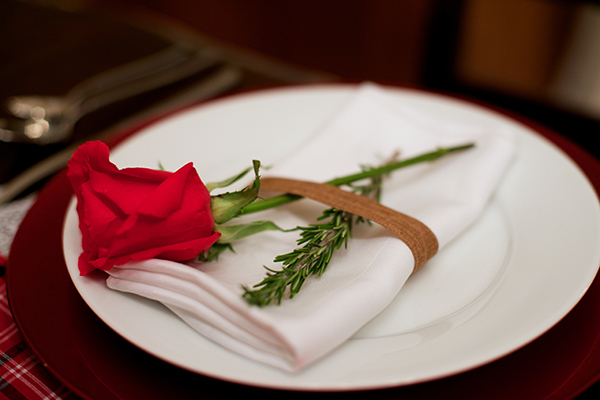 While the rose is beautiful, the green of the stem and the rosemary really add charm with the ruby red chargers.