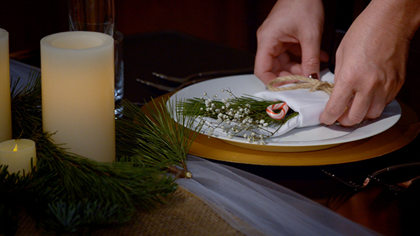 Wrapping the candles in fresh evergreens helps make them pop off of the table.